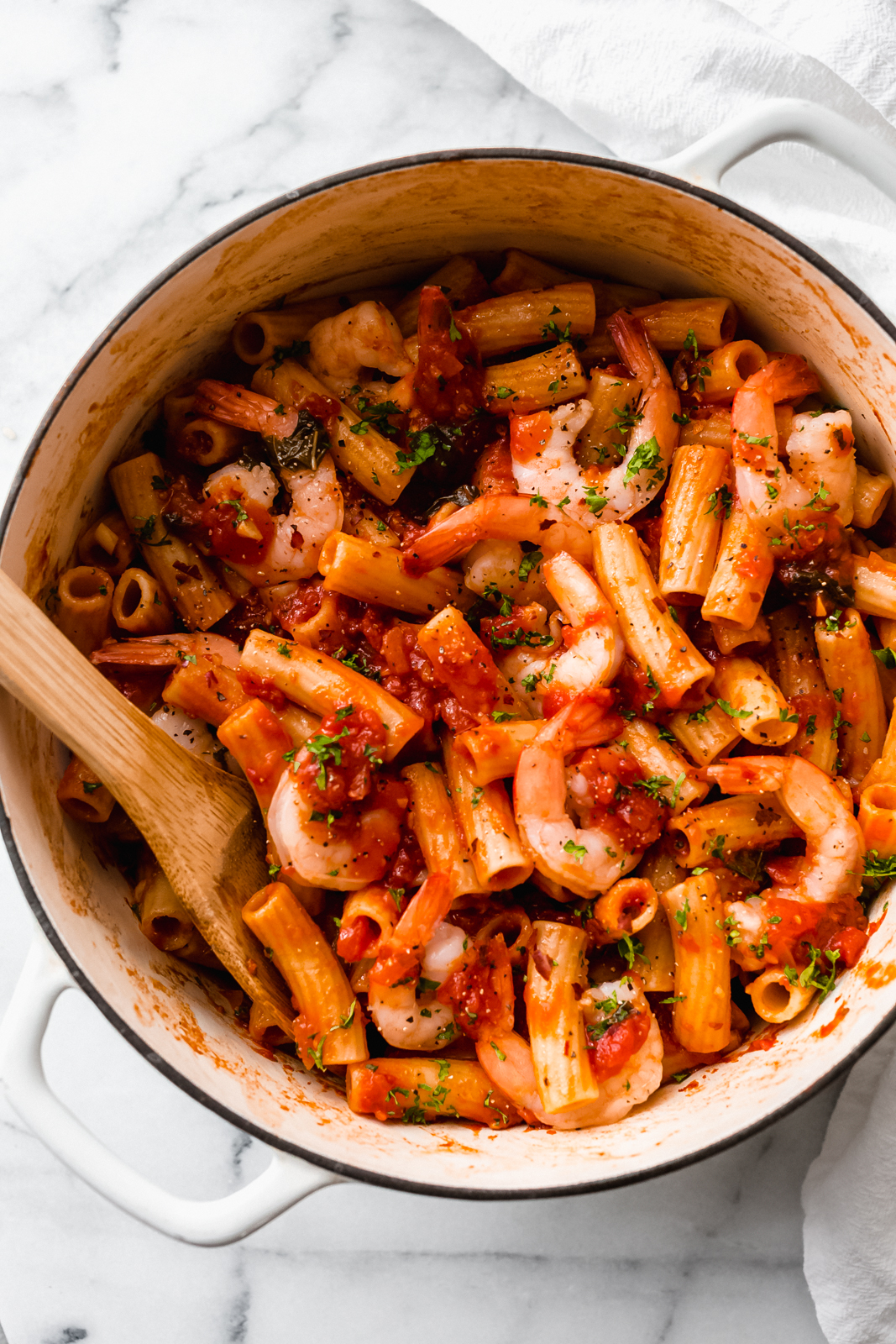 white cast iron pot with prepared pasta with shrimp and sauce