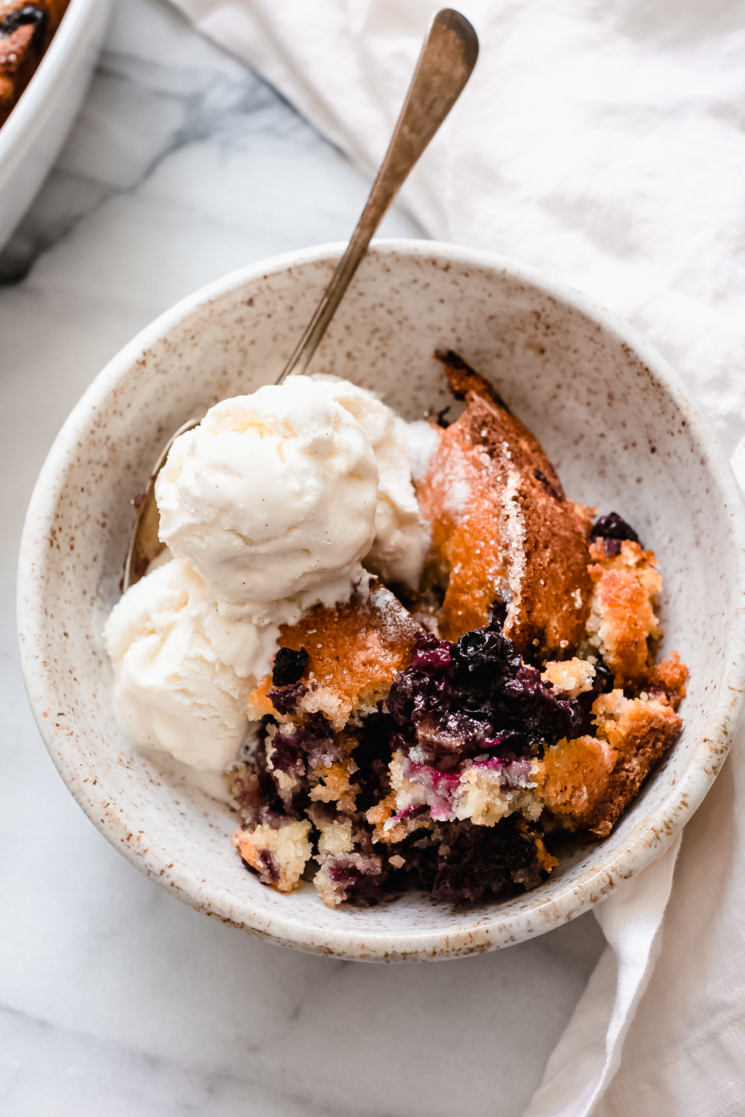 bowl with crumbled conbbler with melting vanilla ice cream and spoon