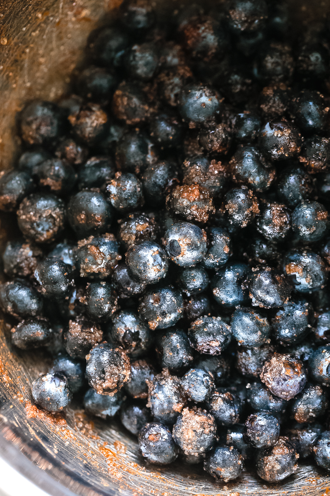 stainless steel bowl with blueberries tossed in sugar and cinnamon mixture