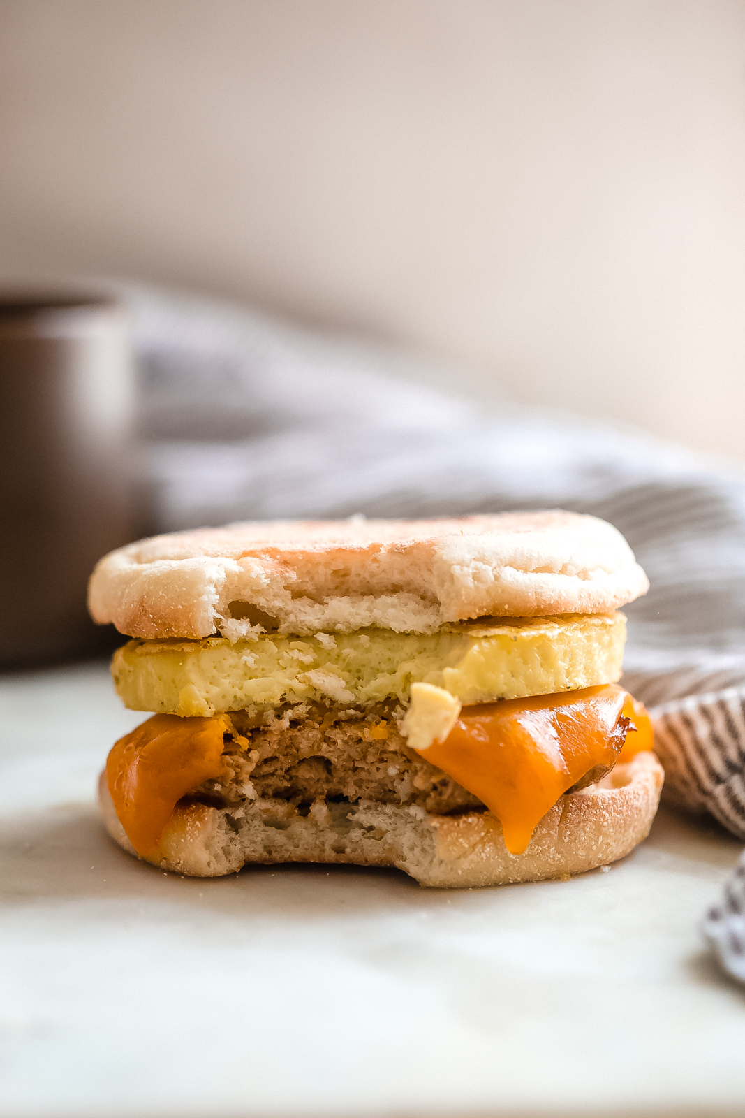 chicken sausage breakfast sandwich with a bite missing on white marble