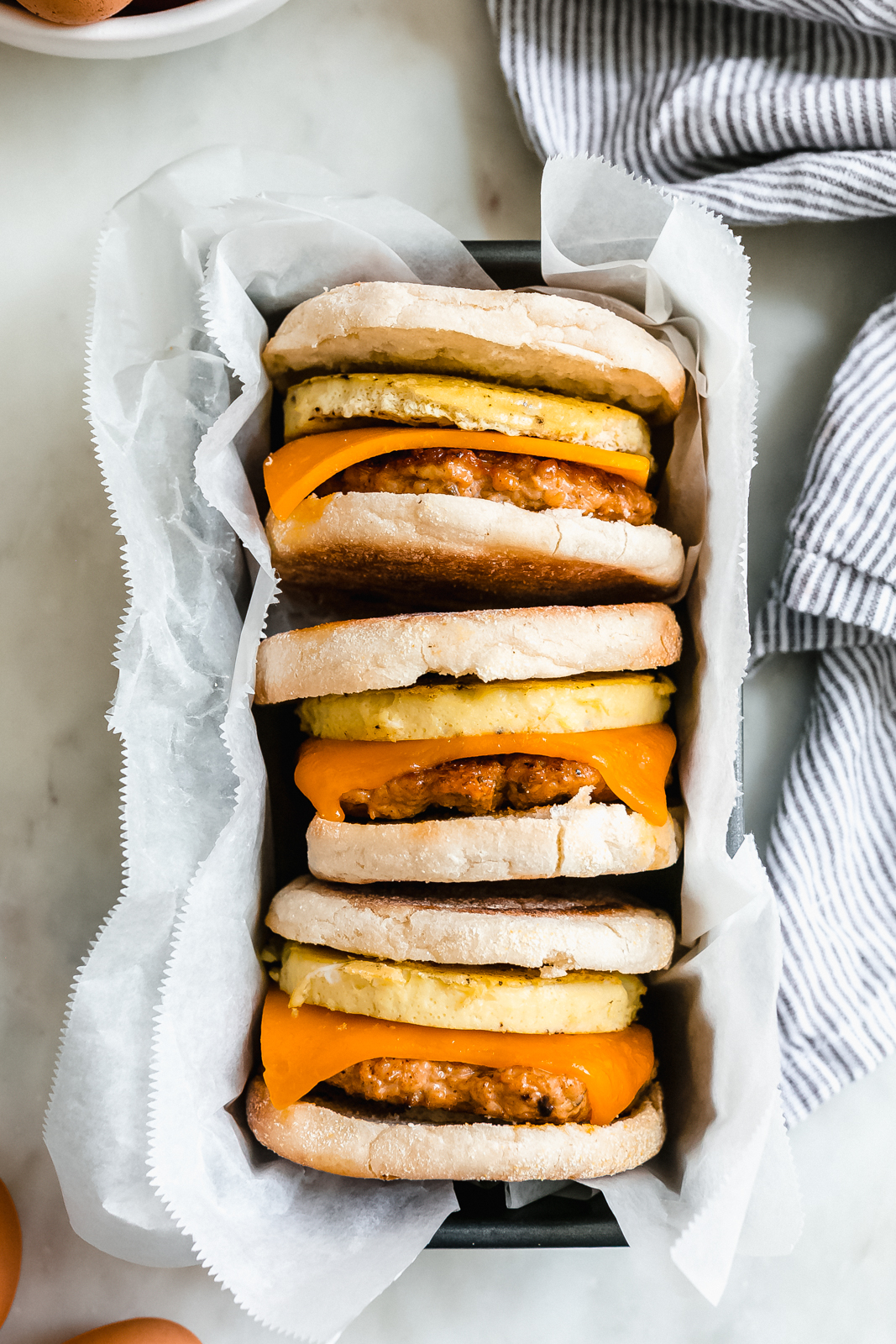 three breakfast sandwiches in a loaf pan lined with wax paper