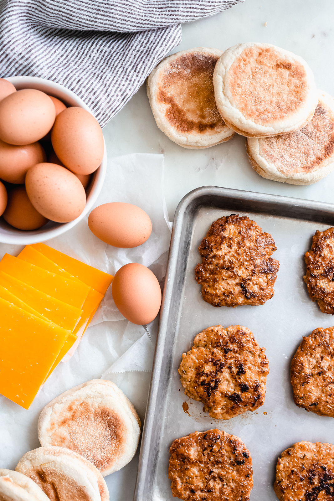 all the ingredients needed to make freezer breakfast sandwiches on white marble