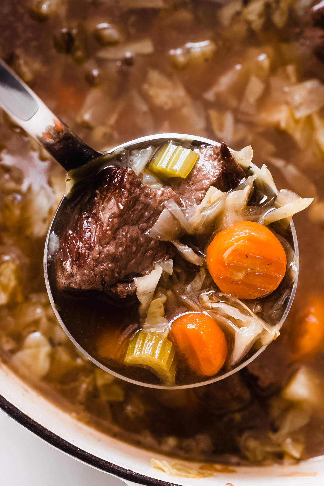 ladle with soup showing carrots, celery, cabbage and stew meat