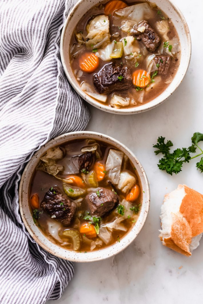 bowls of cabbage beef soup on white marble