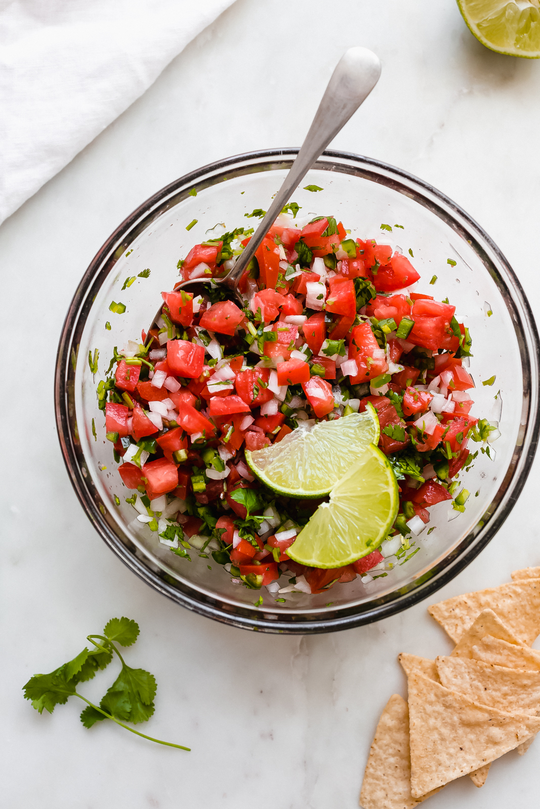 glass bowl with tossed pico de gallo topped with lime wedges on white marble