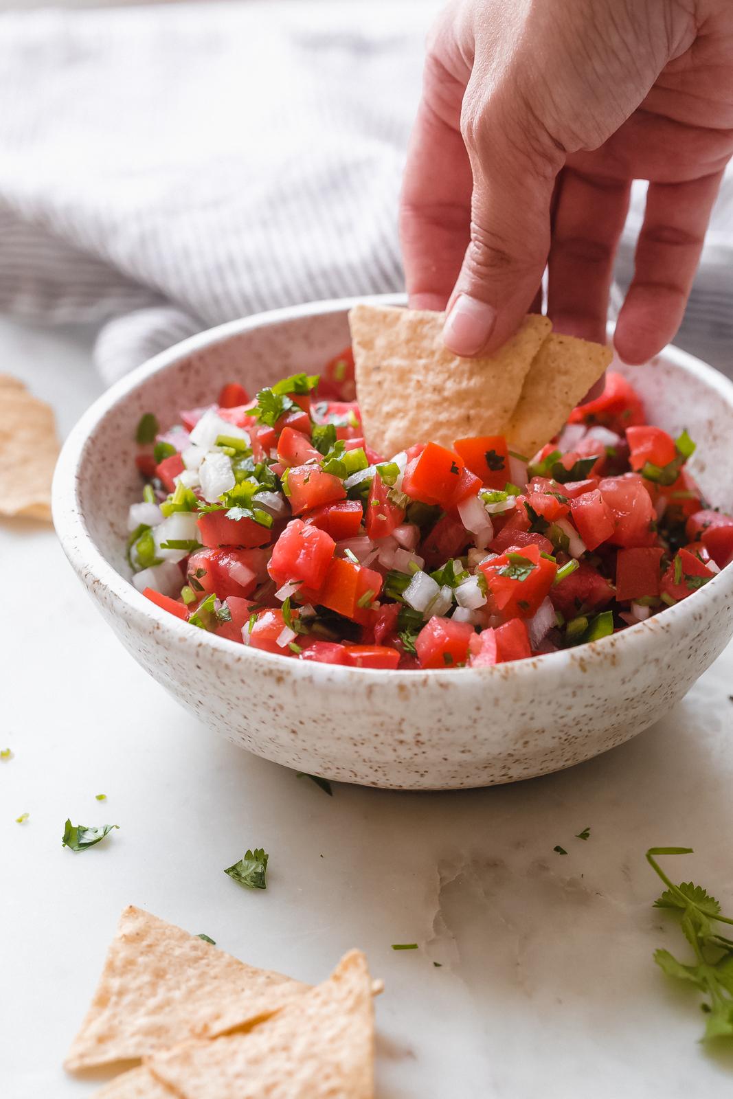 hand dipping tortilla chips into bowl with pico de gallo