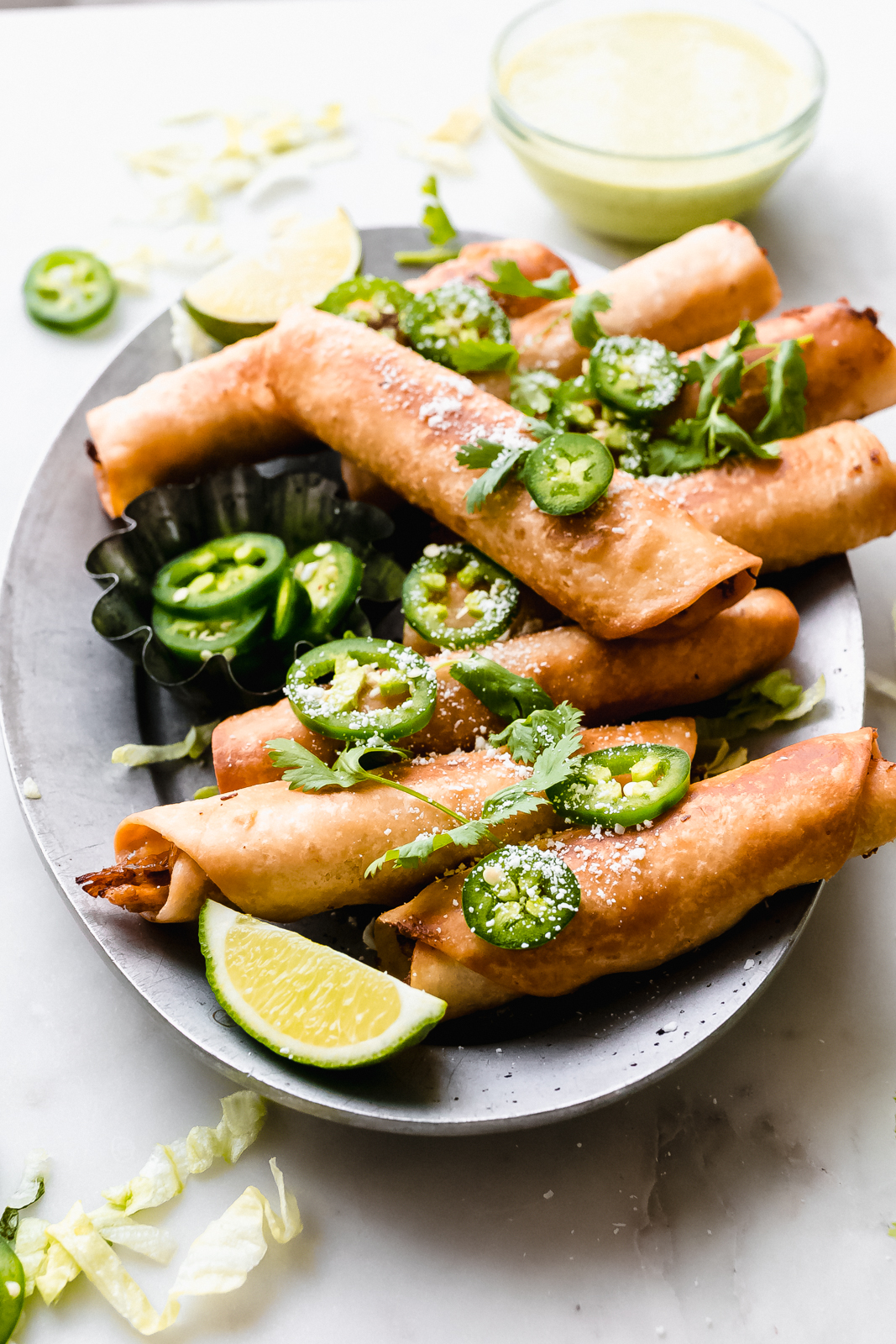 metal plate with prepared fried taquitos sprinkled with jalapeño slices, cilantro, and cheese