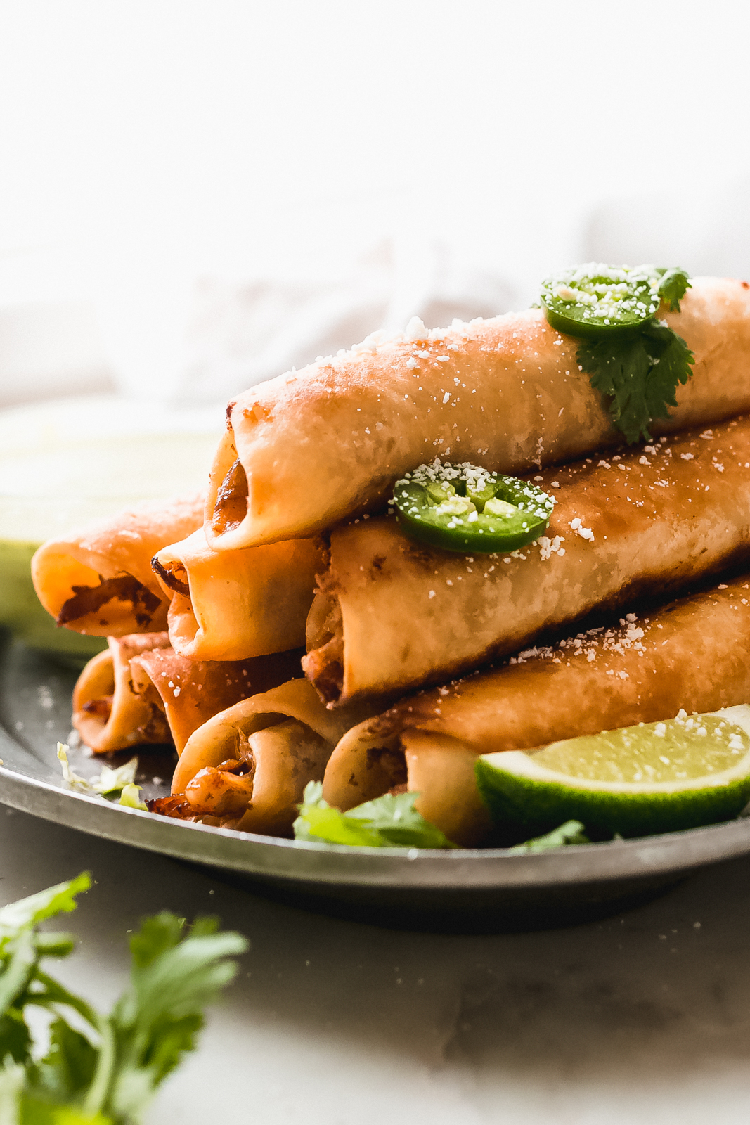 stack of fried taquitos topped with crumbled cheese and jalapeño slices