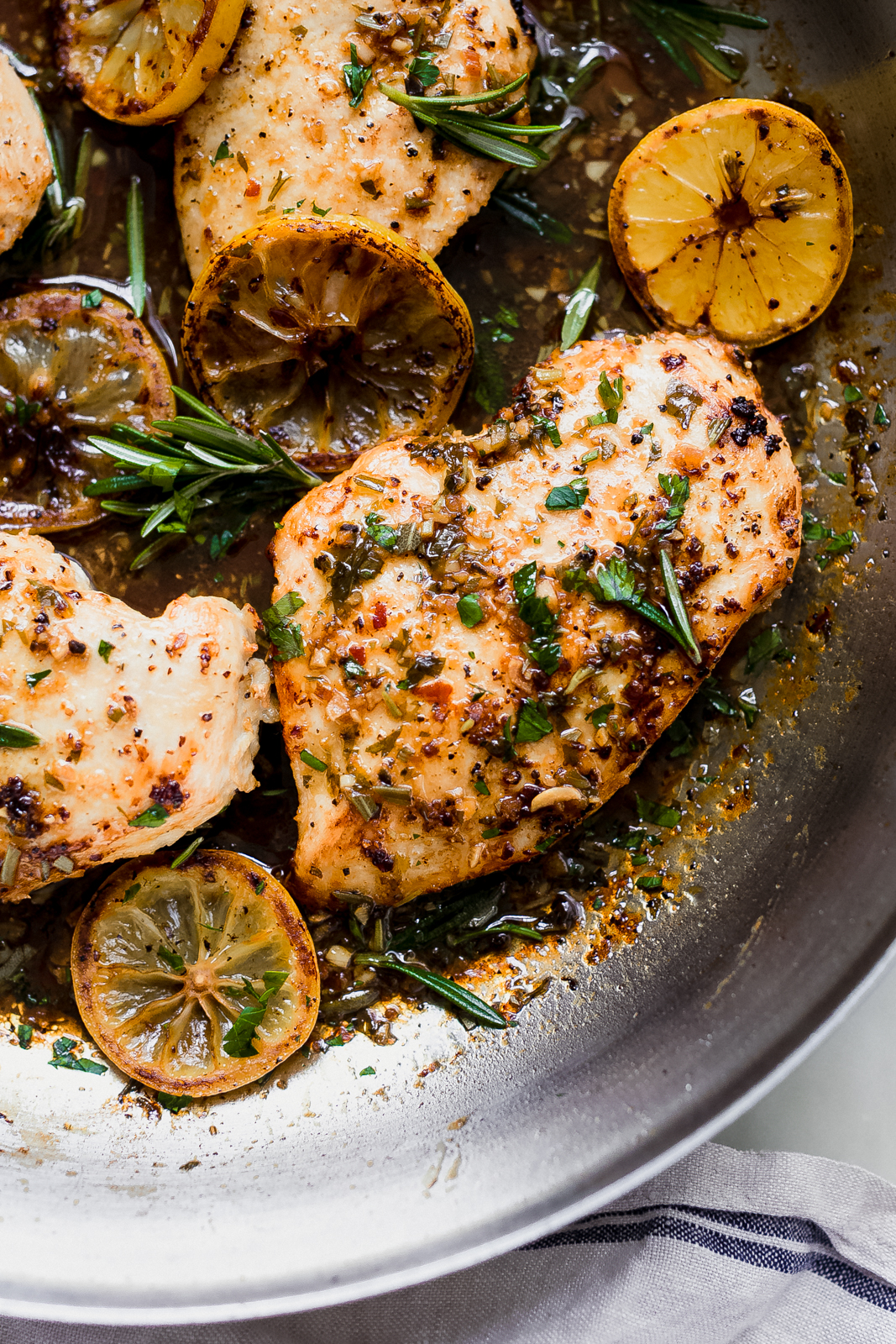 lemon rosemary chicken in a skillet with pan sauce, herbs, and lemon slices