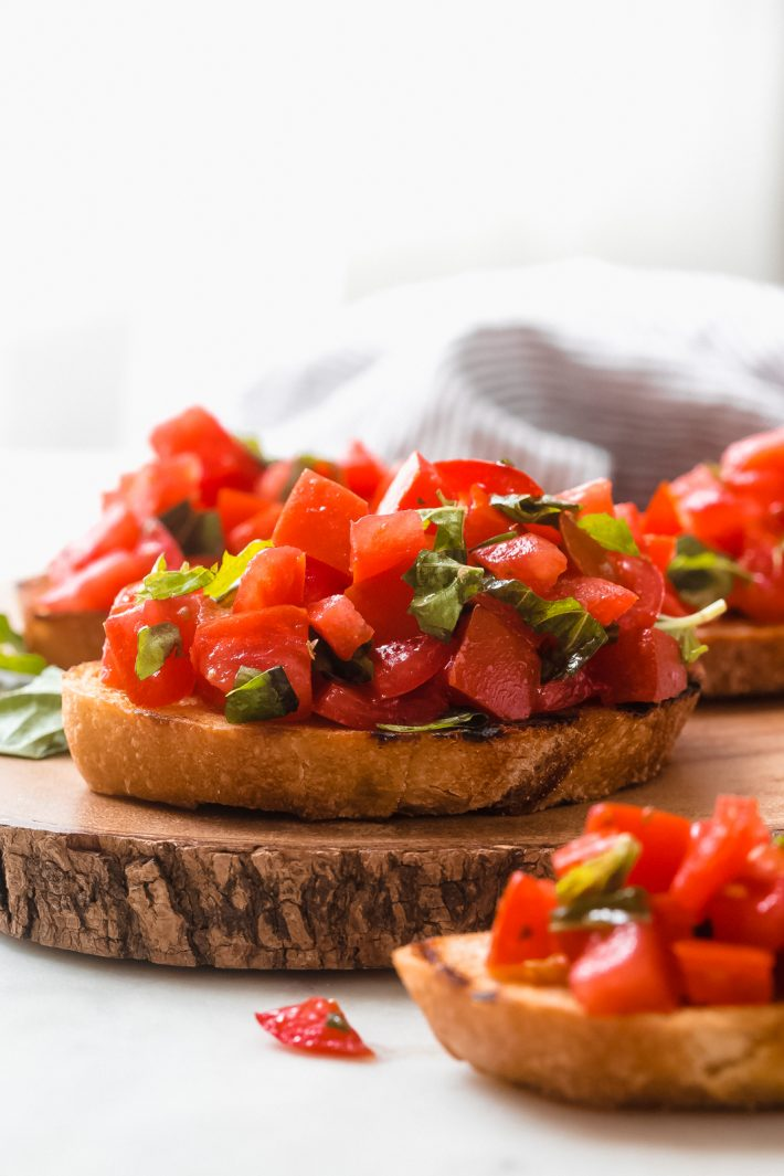 slices of crusty baguette topped with chopped tomato and basil on wood surface