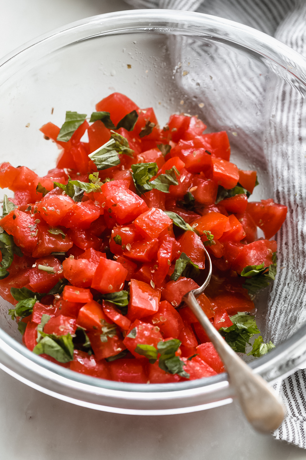fresh tomatoes and basil tossed with seasonings in glass bowl with spoon