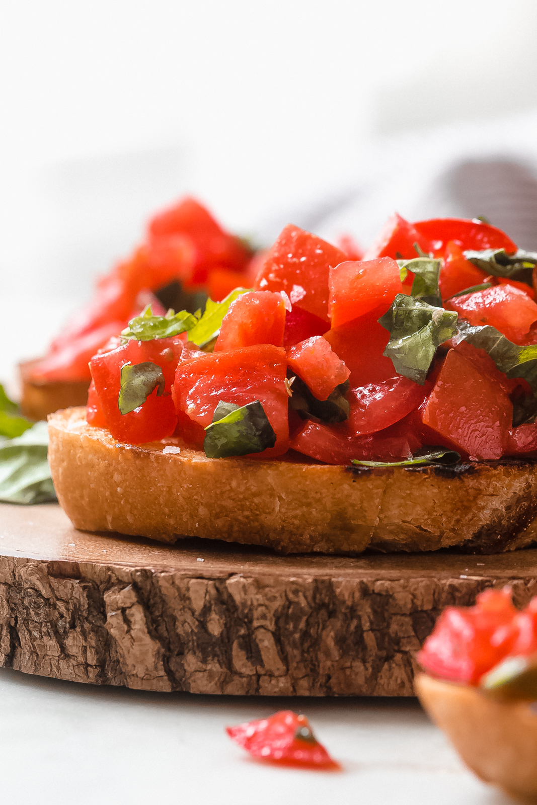 fresh tomatoes and basil on garlic scented baguette on wood surface
