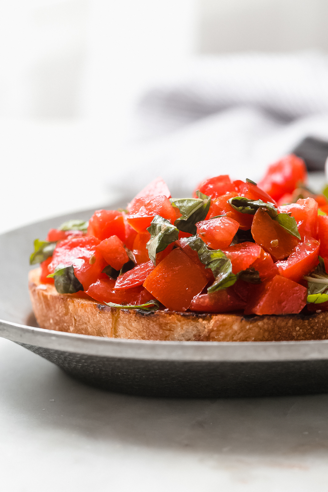 close up of toasted bread topped with tomato basil bruschetta mixture on metal plate