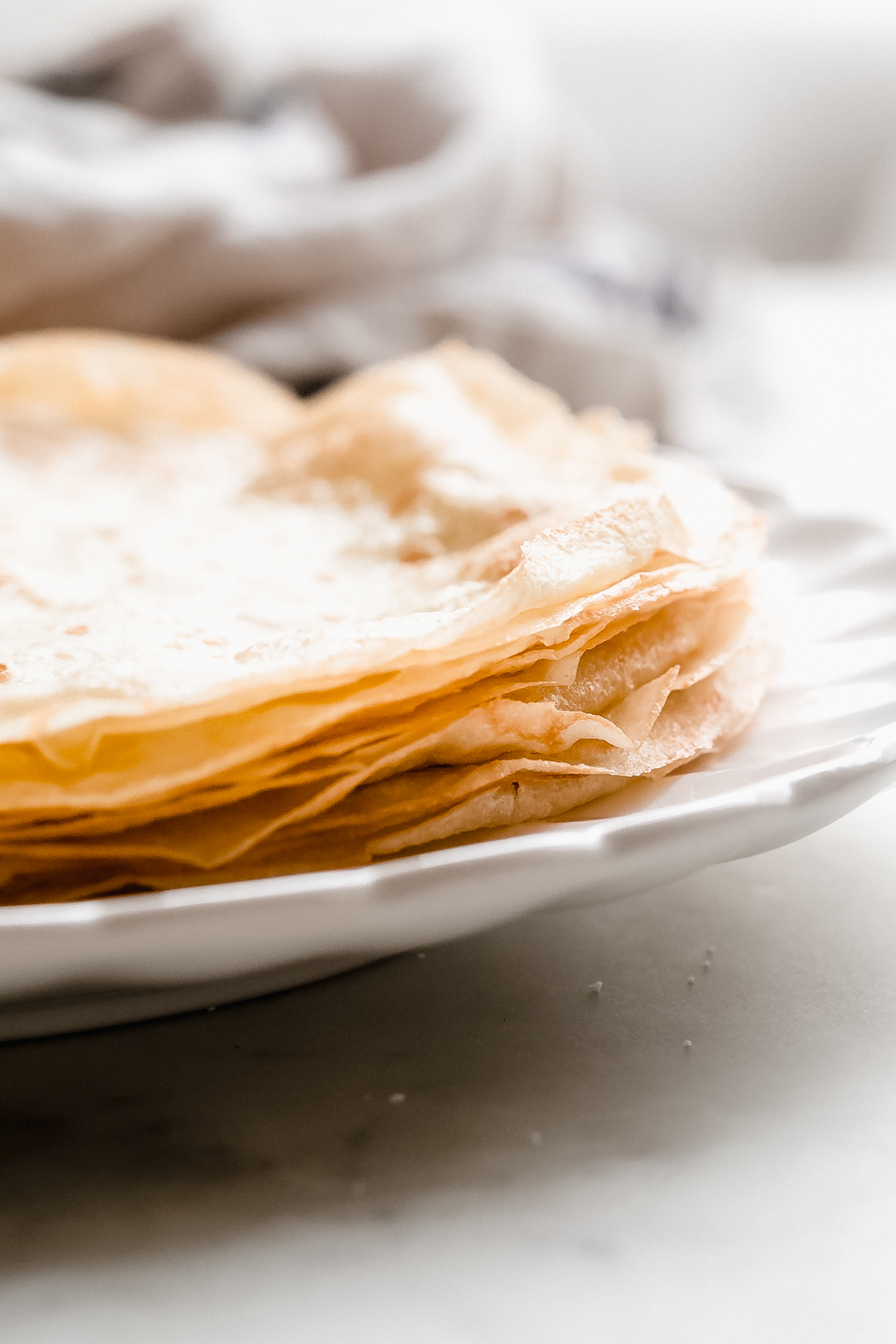 stack of prepared crepes on a white plate on marble surface