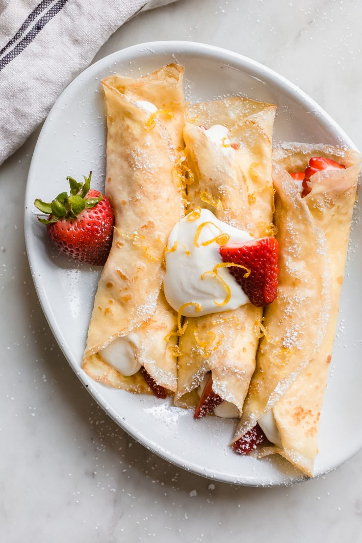 three rolled crepes on oval white plate stuffed with lemon whipped cream