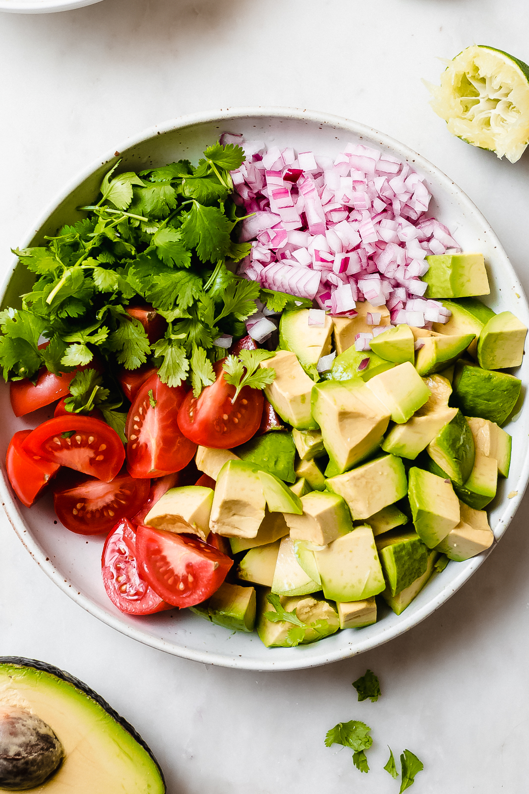 white bowl with topped avocados, tomatoes, minced onions, and cilantro on marble