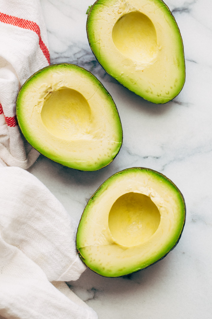 avocados cut in half with the pit removed on marble