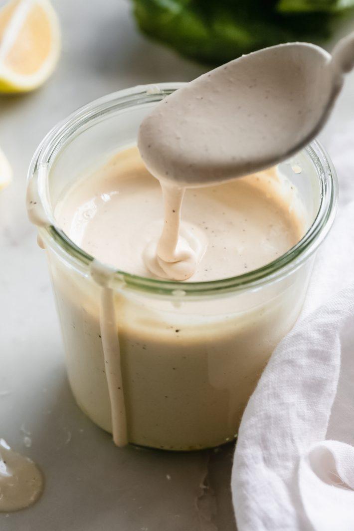 prepared creamy Caesar salad dressing dripping from spoon into jar