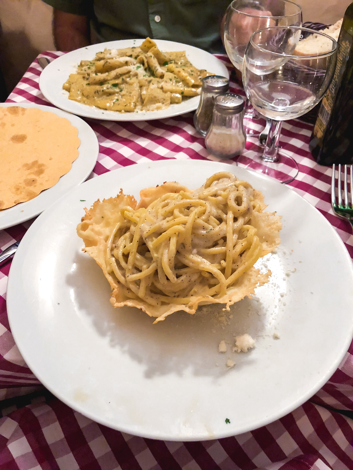 cacio e pepe in a parmesan bowl on a white plate