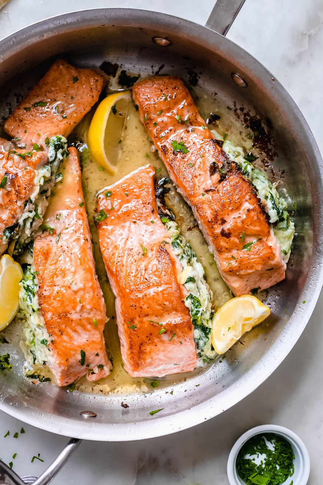lemon butter sauce drizzled on artichoke and spinach stuffed salmon filets