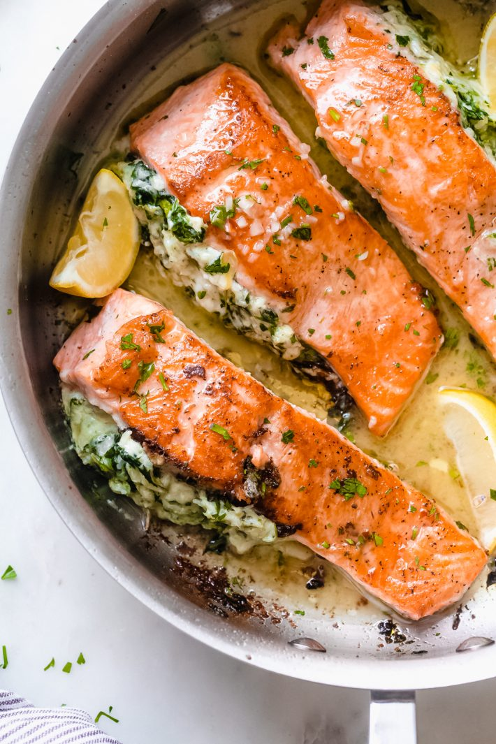 top shot of seared salmon stuffed with spinach artichoke dip and drizzled in lemon butter sauce