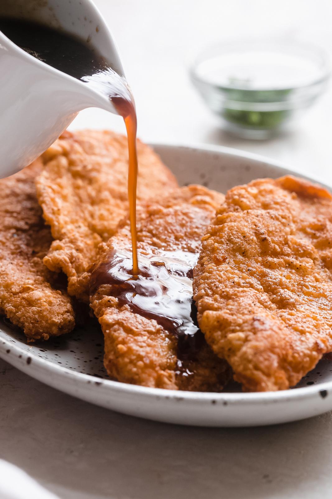 pouring honey garlic sauce over crispy chicken breasts