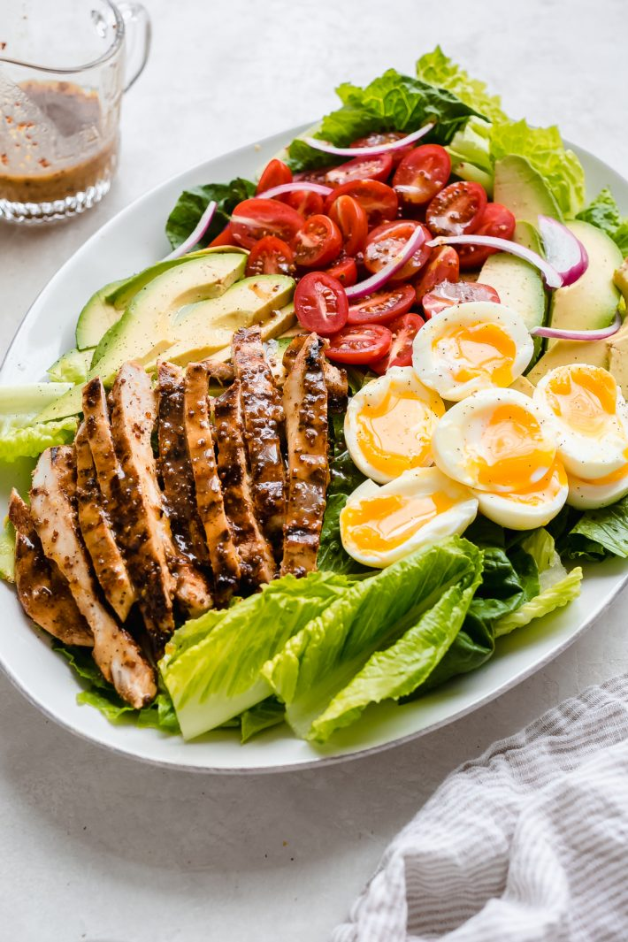 Honey Mustard Chicken Cobb Salad - An easy cobb salad where the dressing doubles as a marinade for the chicken. Served with soft boiled eggs, cherry tomatoes, and sliced avocados #chickensalad #chickencobbsalad #chicken #salad #cobbsalad | Littlespicejar.com
