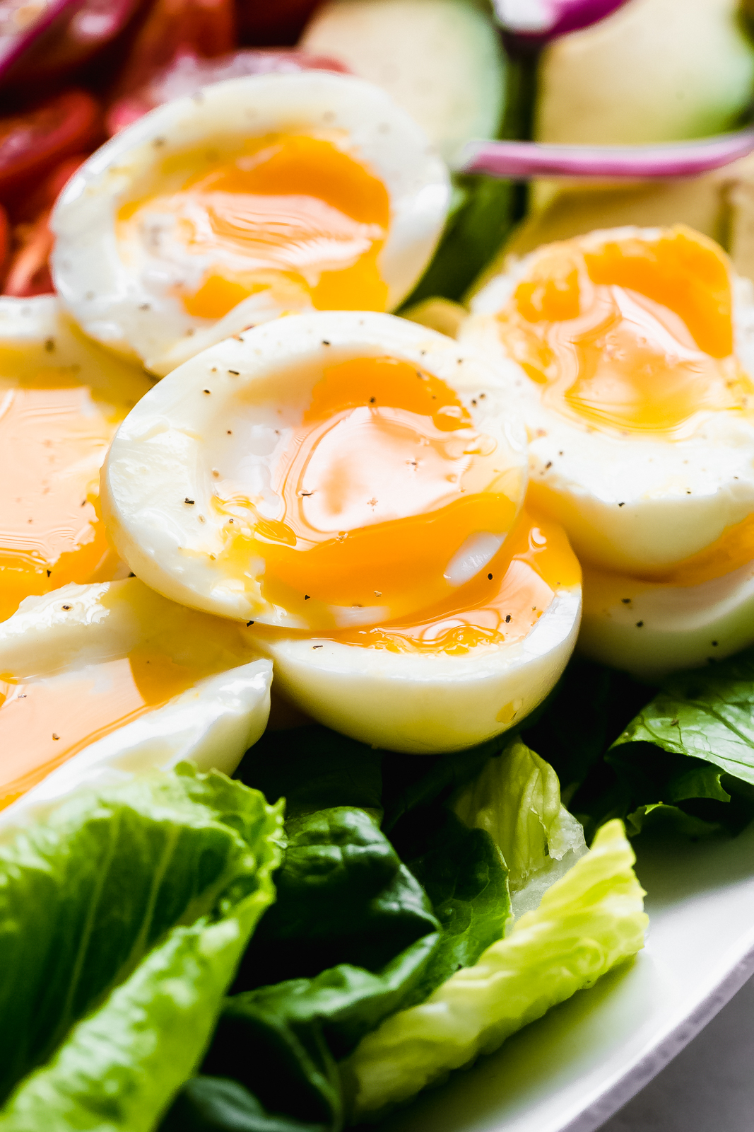soft boiled eggs with dripping yolks on lettuce