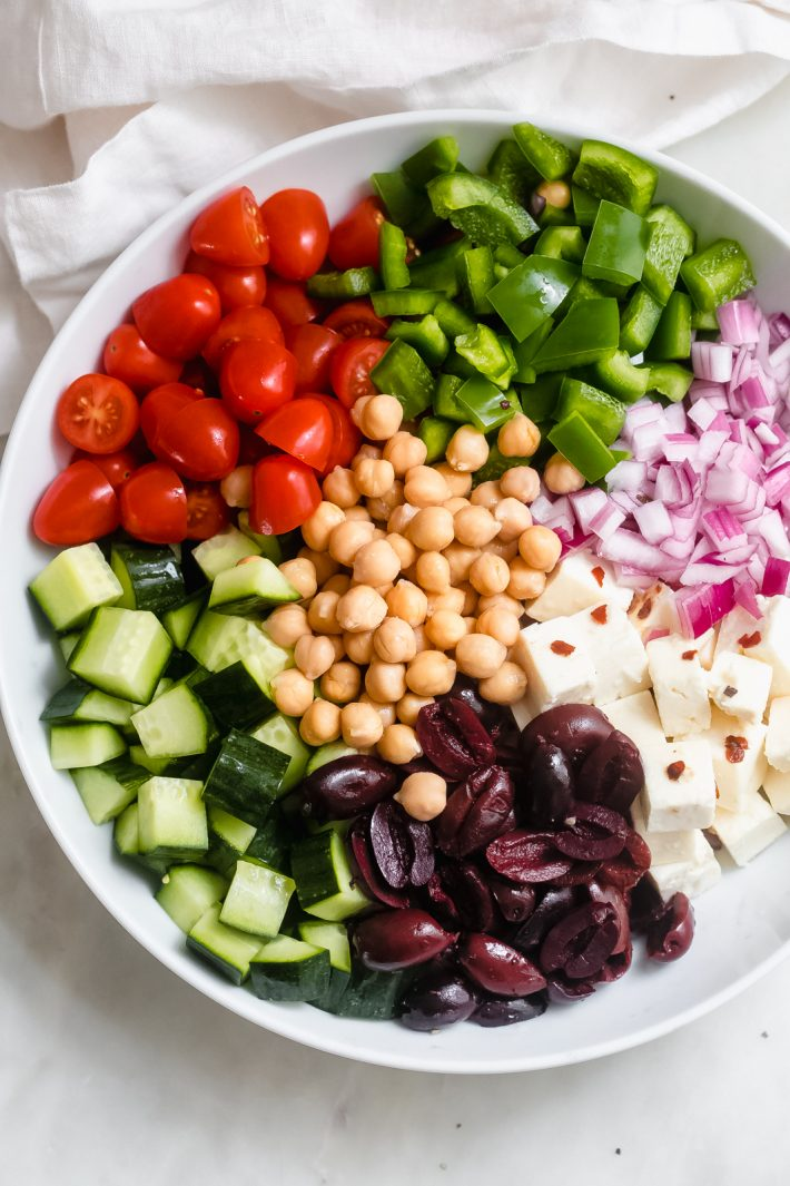 ingredients for greek salad in a white bowl