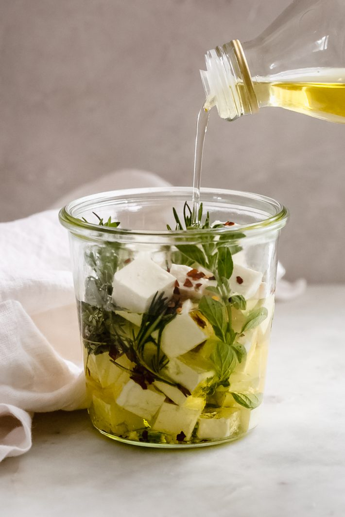 pouring oil into a glass jar with herbs and cubed feta cheese