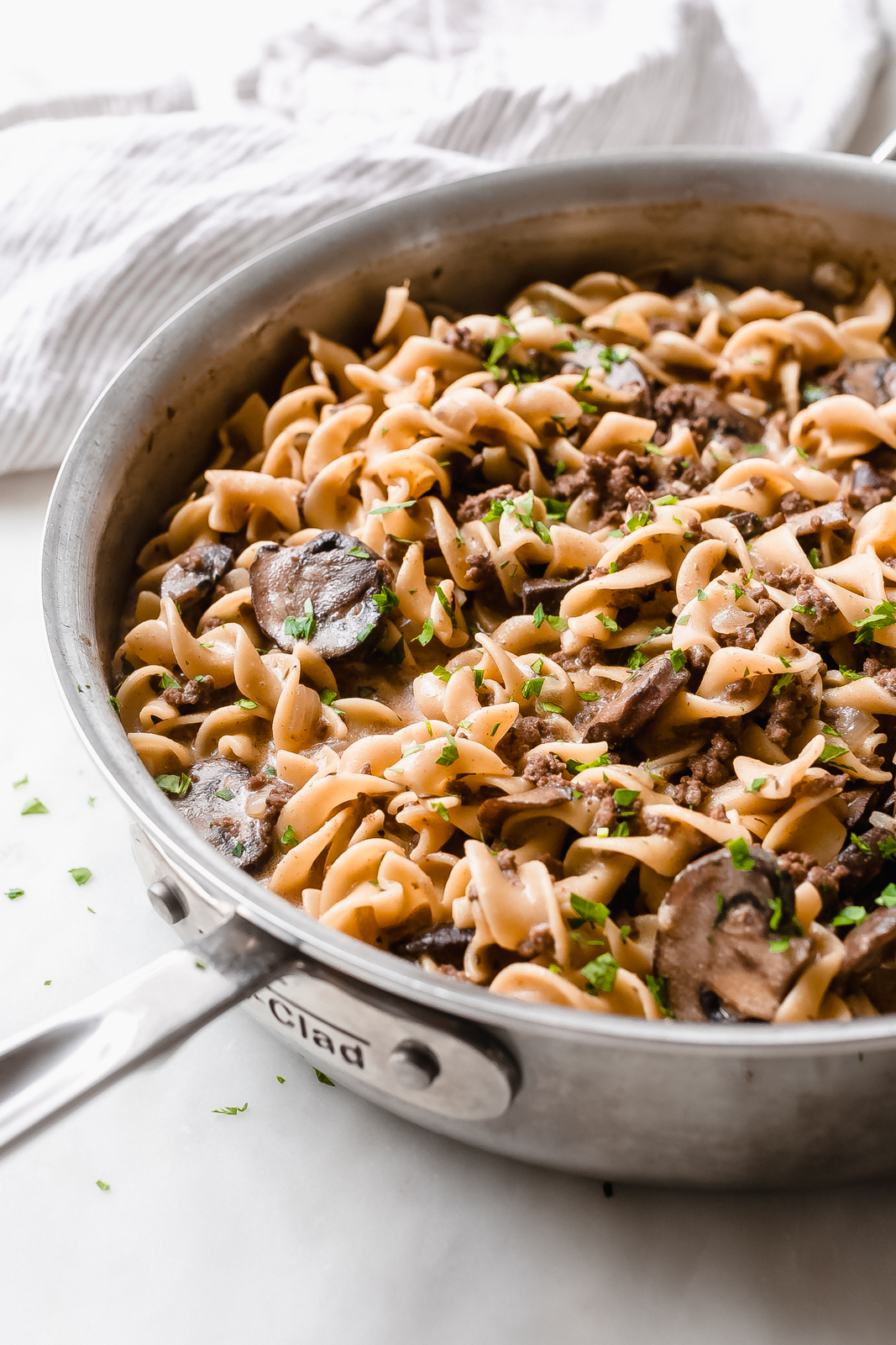 side view of skillet with egg noodles, mushrooms, and ground beef in brown cream sauce