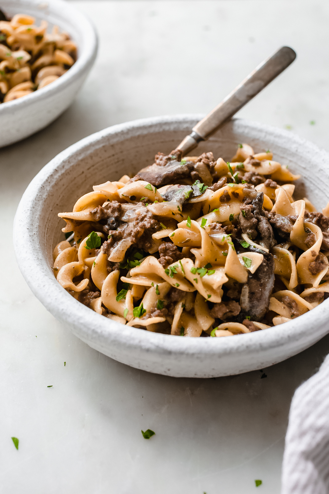 egg noodles with ground beef in a white bowl on white marble