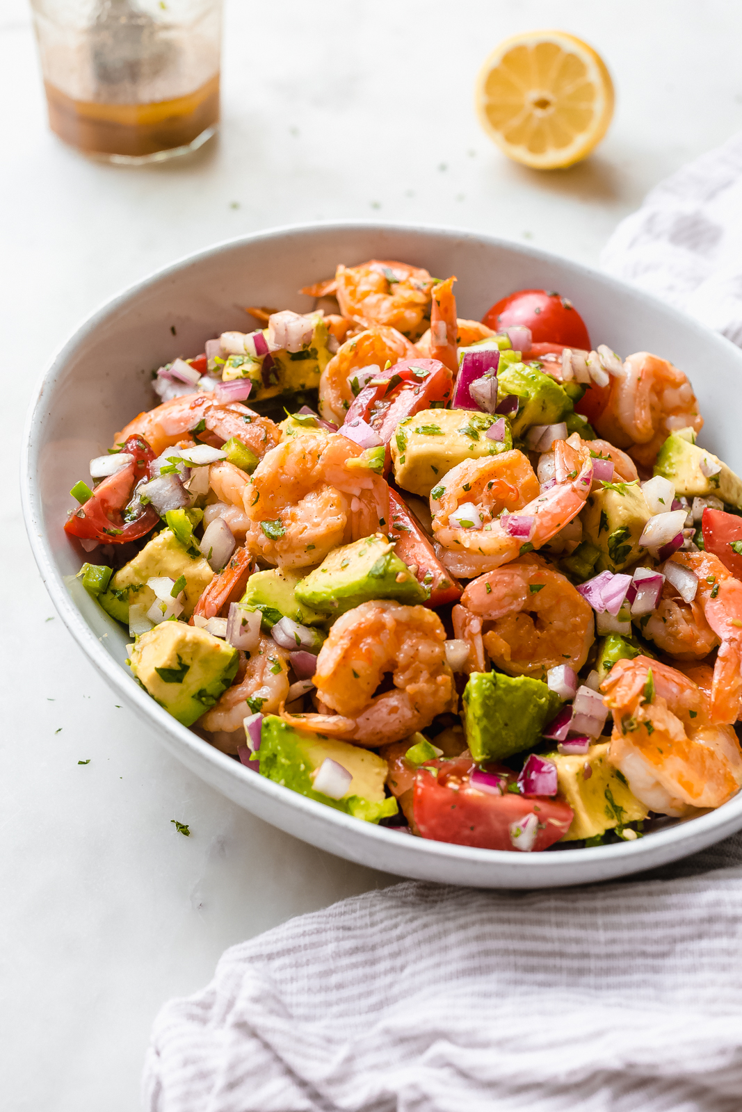 angled view of shrimp salad with avocados dressed in lemon dressing