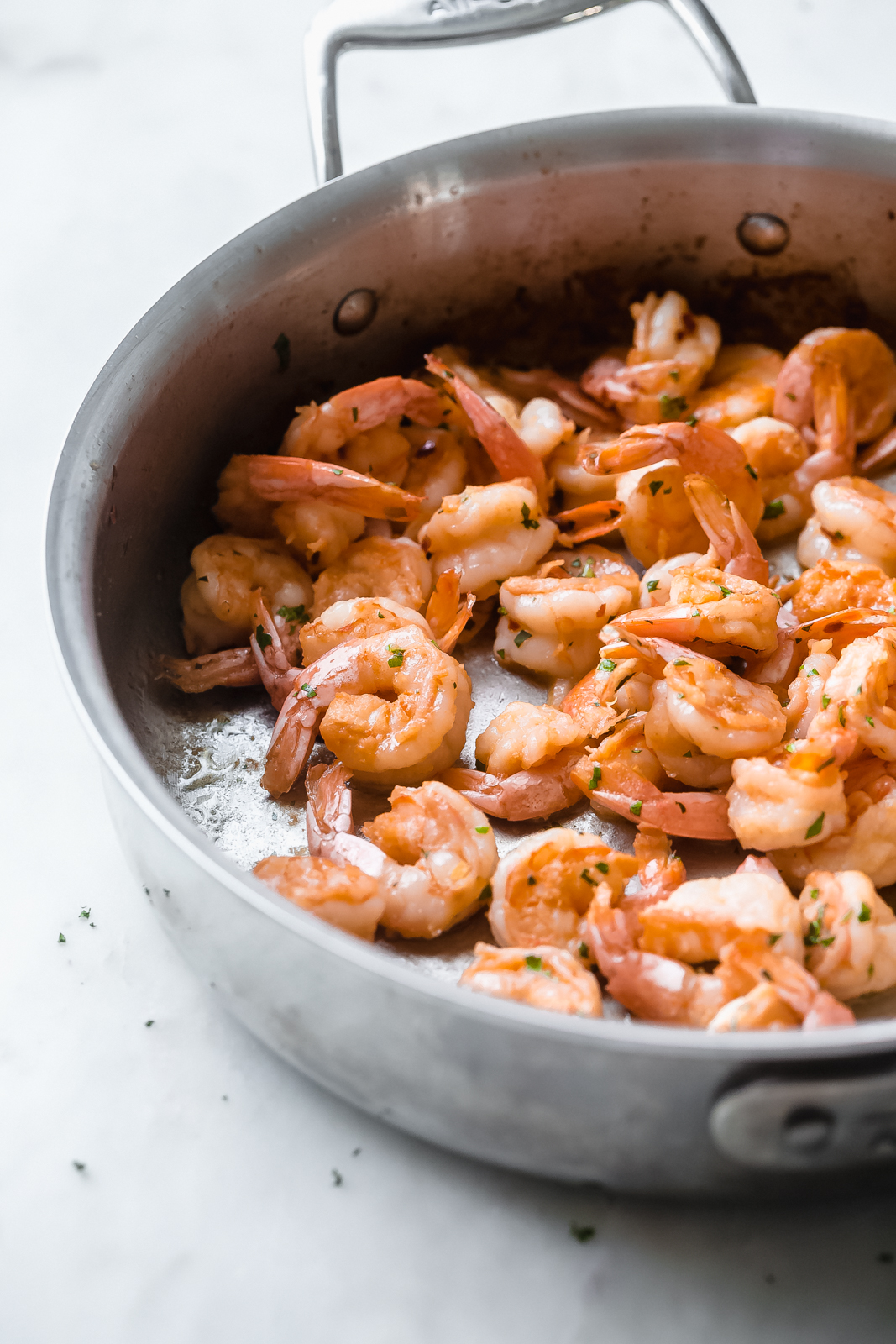 sautéed shrimp in saute pan on white marble surface
