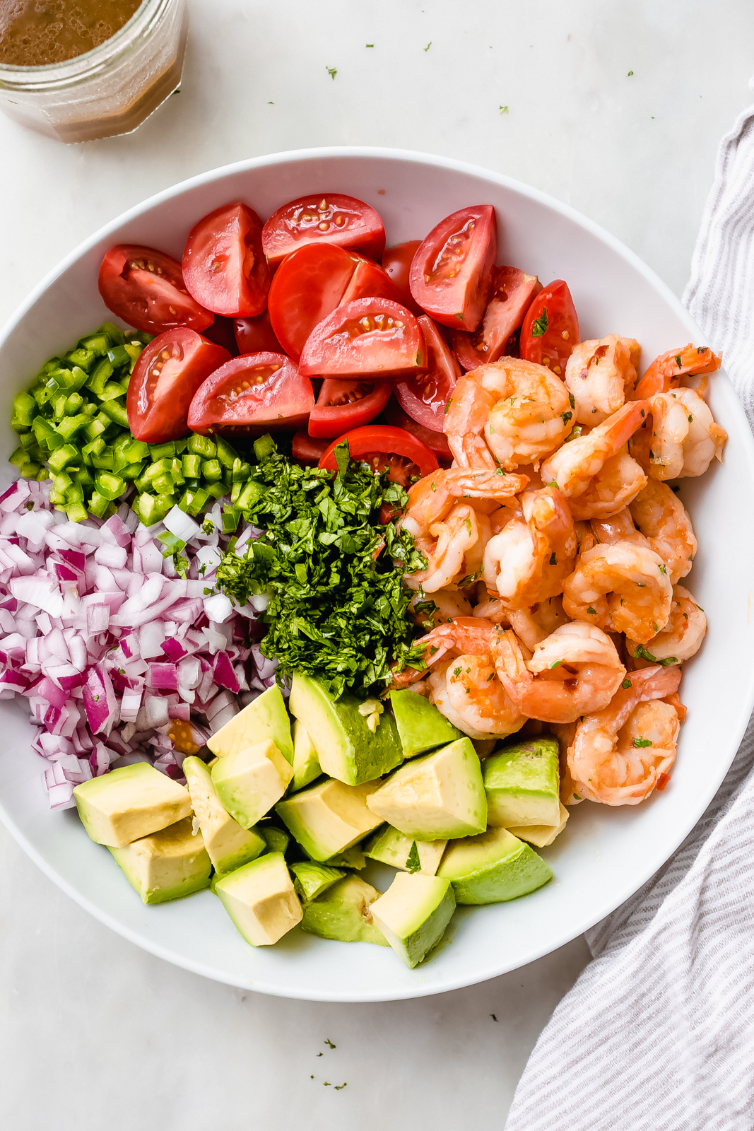 ingredients for Mexican shrimp salad in piles in a large white bowl