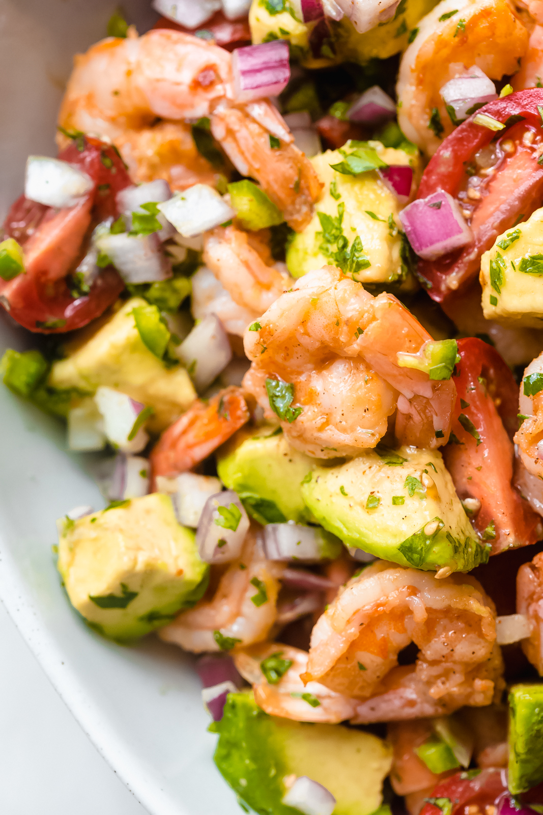 close up of sautéed shrimp salad with avocado chunks, minced onions, tomato wedges, and cilantro