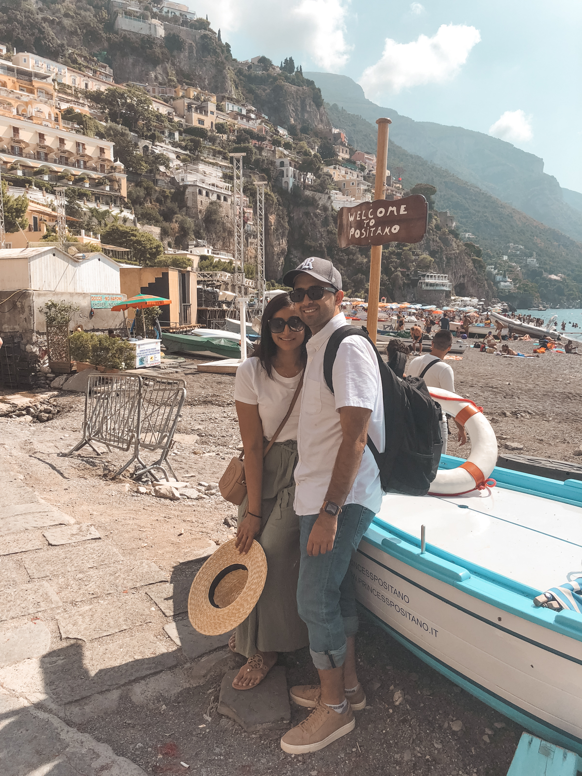 hubby and me with a 'welcome to Positano' sign near the water