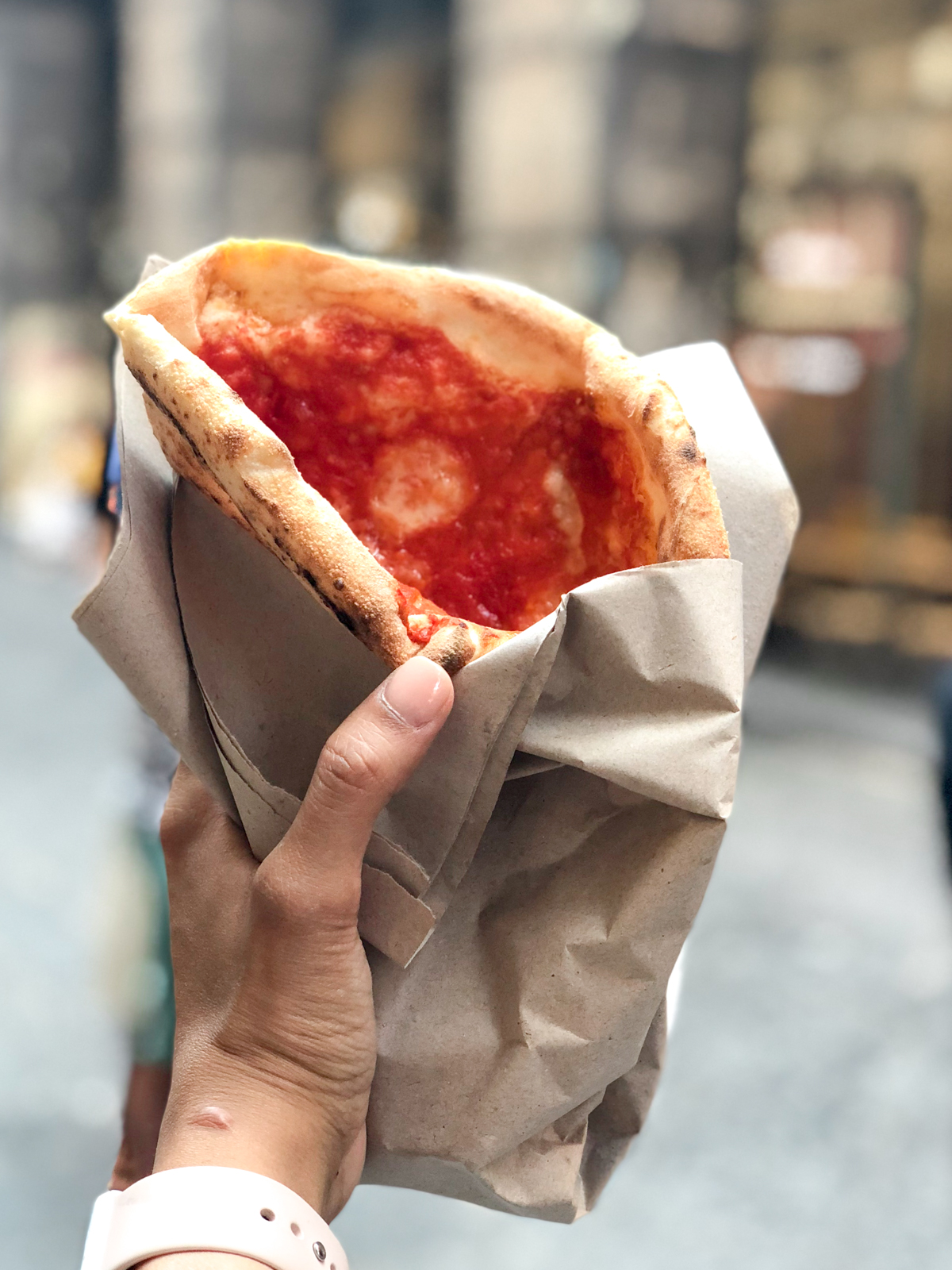 pizza folded like a sandwich in brown paper from Naples