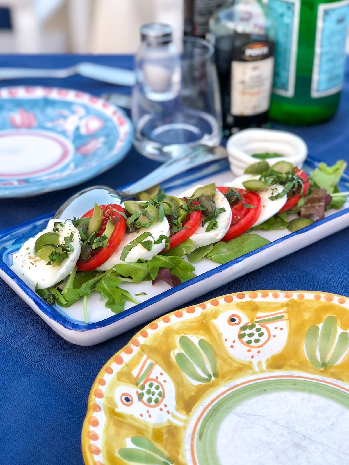 mozzarella, tomato slices, arugula, and olive salad