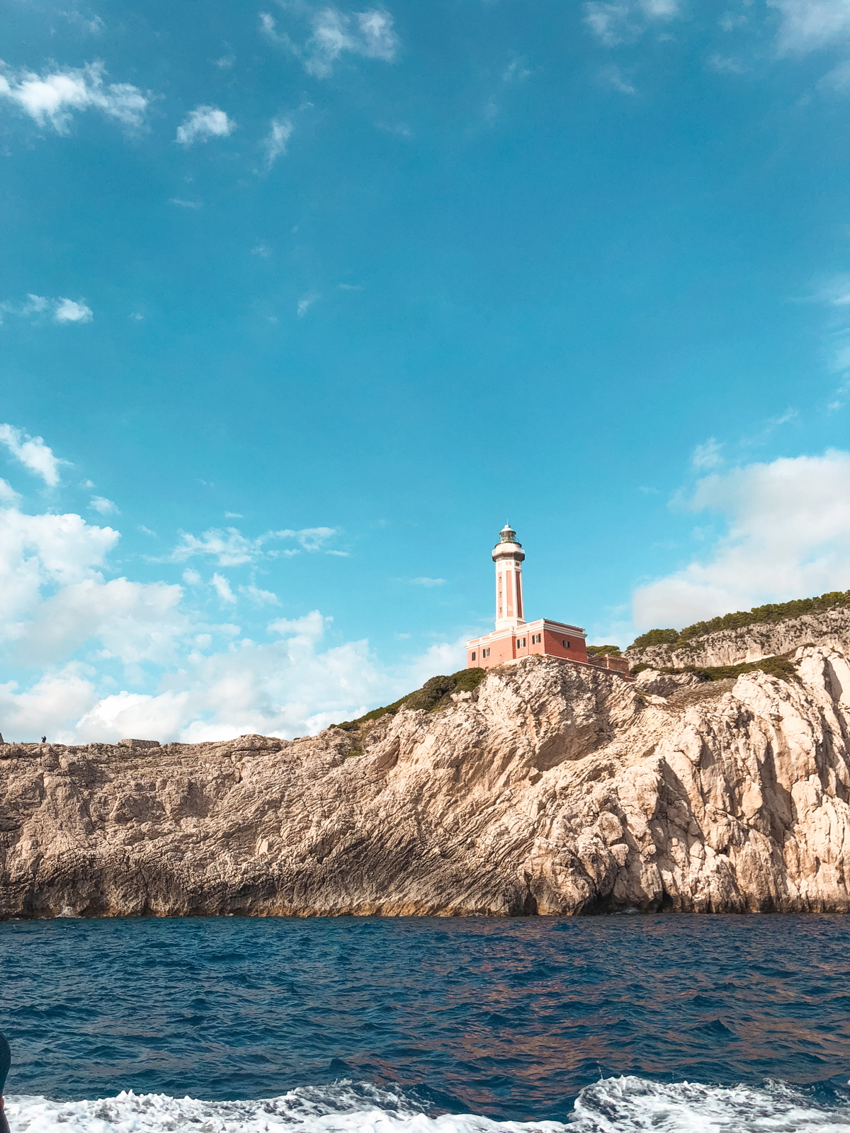 out on the water near capri with a lighthouse in the distance