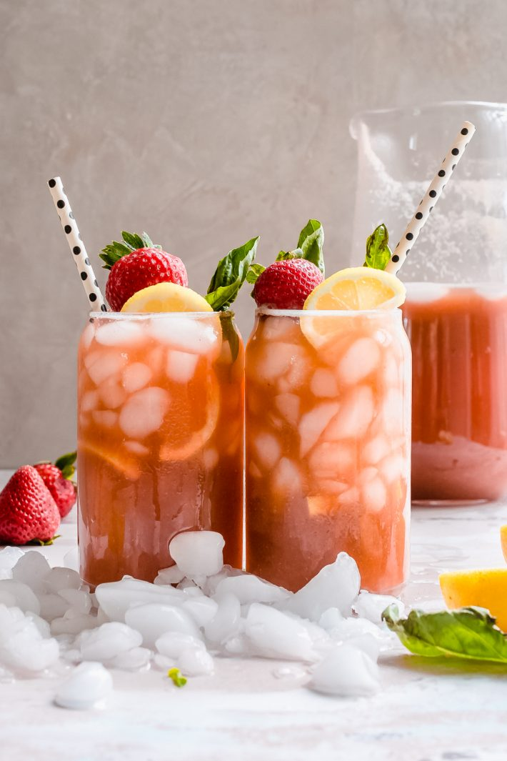 two glasses of strawberry basil lemonade with lots of ice