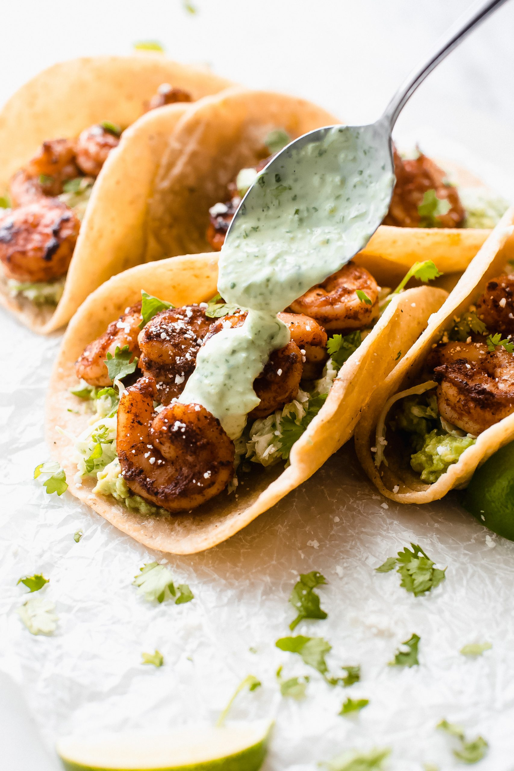 drizzling jalapeno lime crema on blacked shrimp tacos with spoon