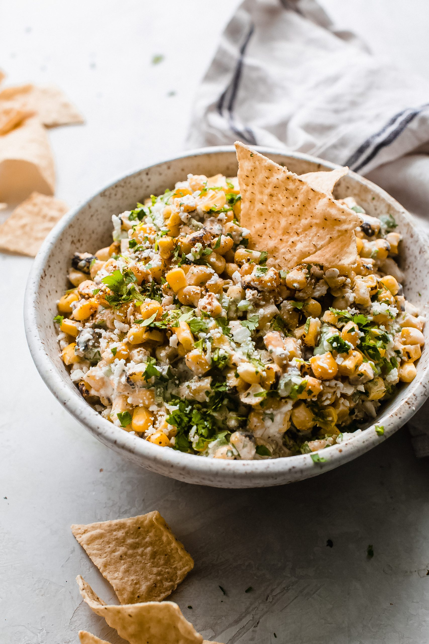 speckled bowl with Mexican corn dip, with tortilla chips standing in bowl