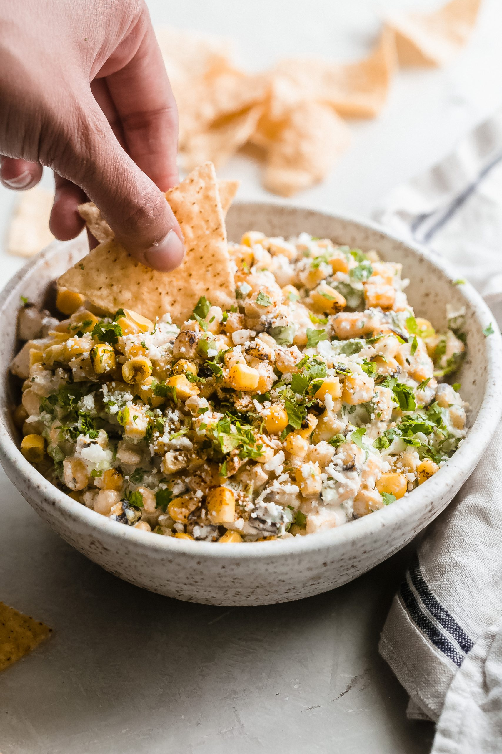 hand dipping corn tortillas in corn dip from bowl
