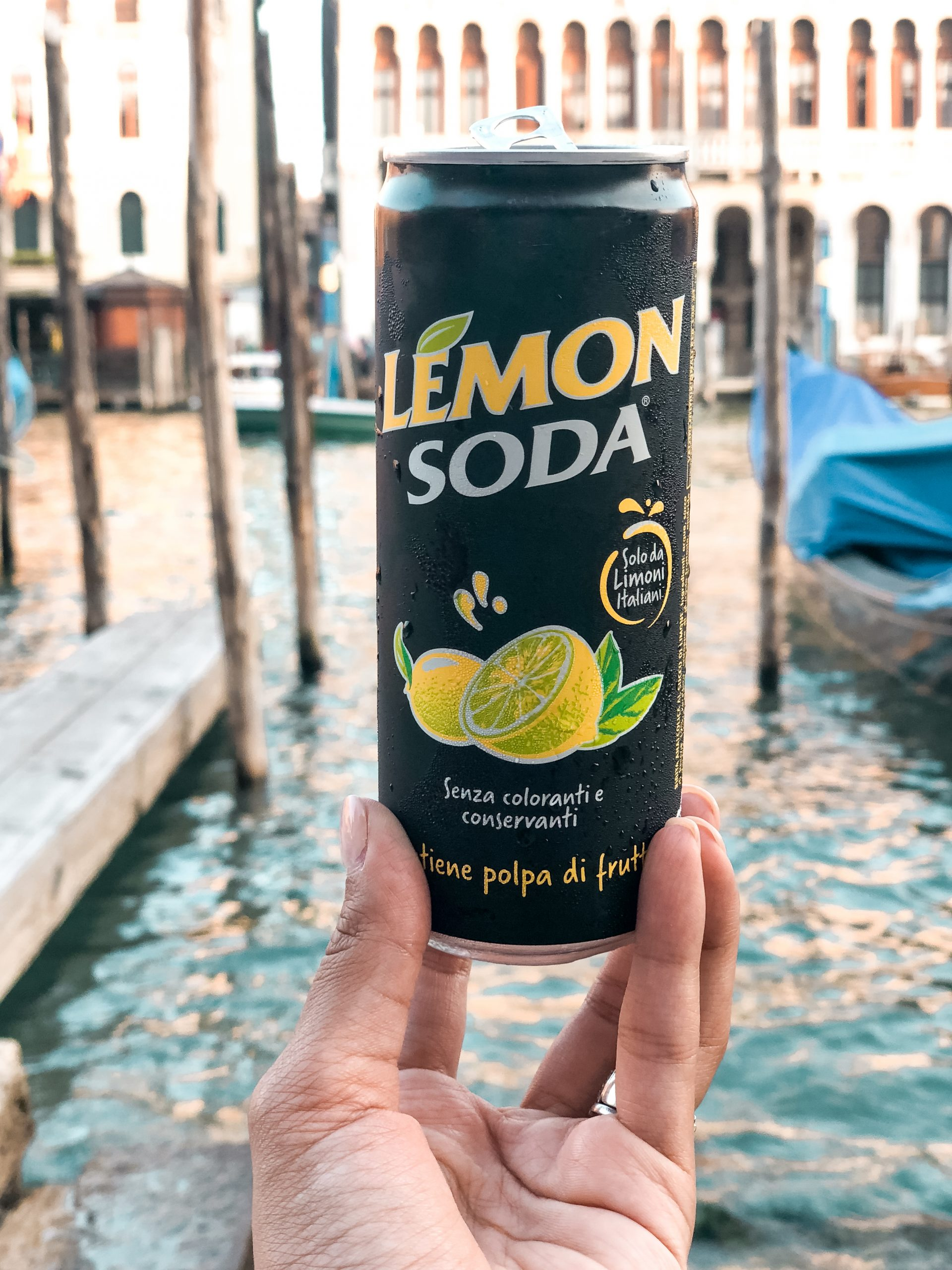 a can of lemon soda with water in the background