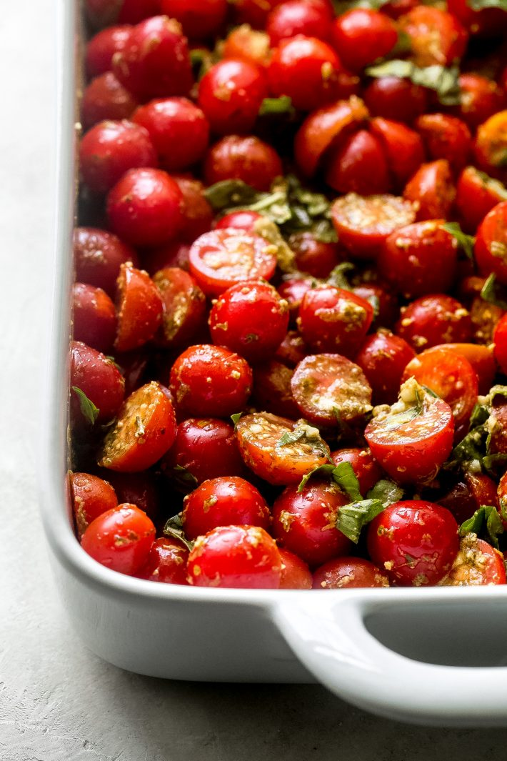 cherry tomatoes tossed with pesto and fresh basil in a baking dish