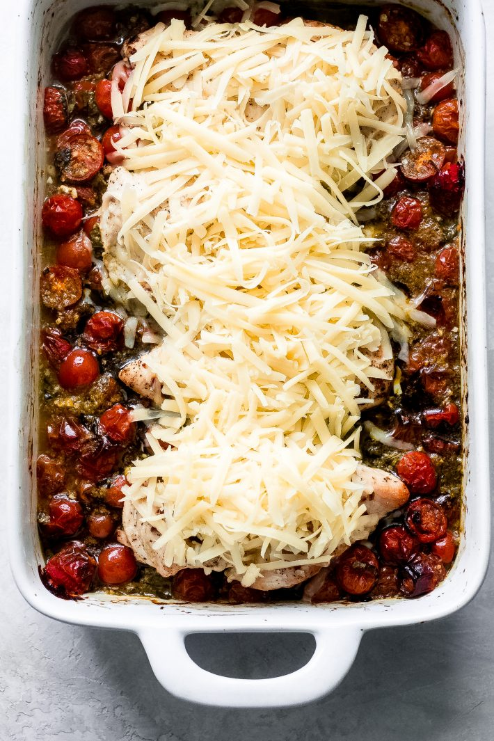 Pesto Baked Chicken with Tomatoes and Mozzarella - an easy dinner idea that comes complete with roasted chicken and tomatoes in a pesto sauce! It's so good and easy to make! #bakedchicken #onepotmeals #chickenrecipes #easyrecipes #dinnerideas #dinnerrecipes #pestochicken | Littlespicejar.com