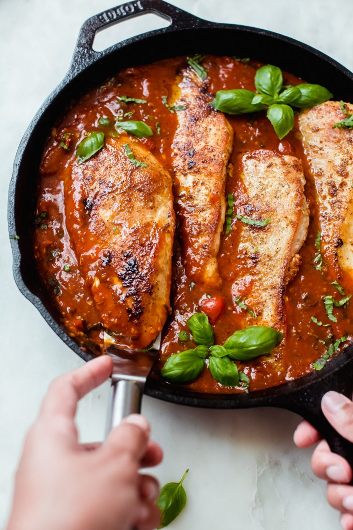 hand lifting chicken filet on spatula from cast iron skillet