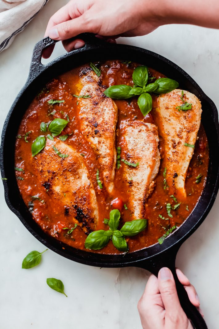 hands holding a skillet with tomato basil chicken
