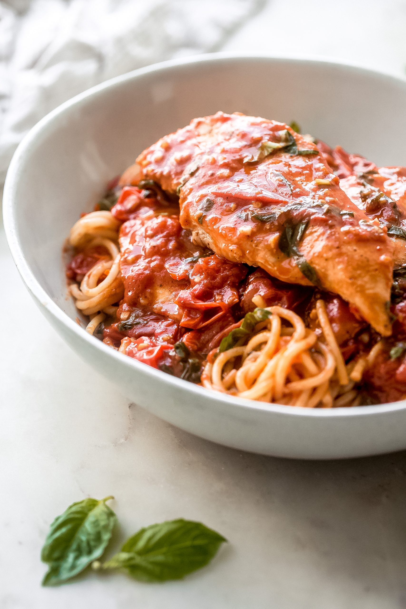 spaghetti in bowl topped with tomato basil pan sauce and seared chicken filet